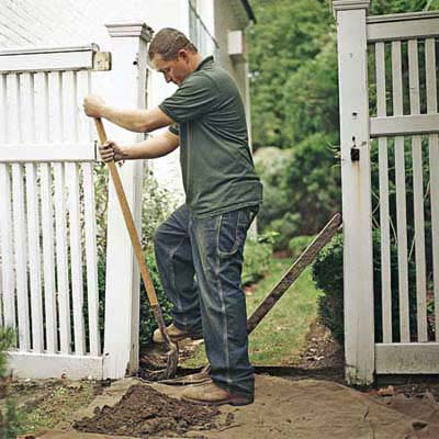 man with shovel by fence