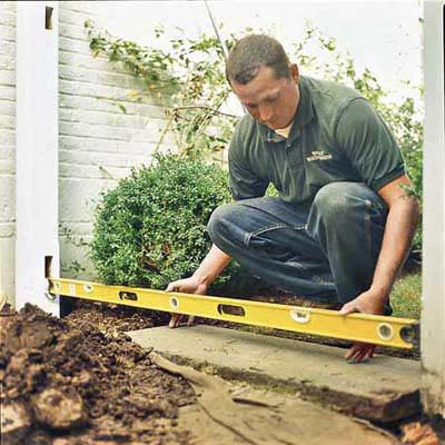 man with measurement tool near ground