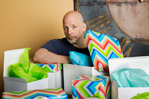 Scott Omelianuk half-buried by gift-wrapped packages