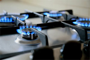closeup of the blue flaming gas burners on the cooktop of a stove