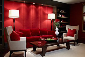 formal living area with no natural light, upholstered red wall, modern furniture, built-in bookcase, recessed lights, and matching floor lamps