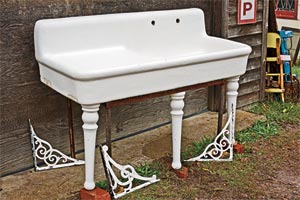 vintage porcelain long-body kitchen sink propped up against an exterior wall with bricks under it's feet, and salvaged metal brackets strewn around it on the ground