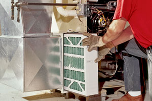 a worker kneels next to a forced-air heating unit pulling out a large, rectangular filter that looks clean as new