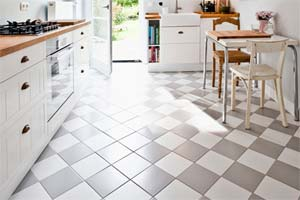 a bright, open kitchen with a grey and white tile floor installed in a diamond pattern. a door to the outside yard is open at the back