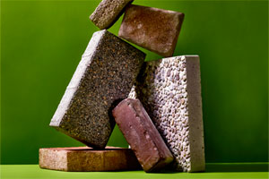 stack of concrete pavers in different sizes, textures, and colors against a green background