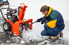 roger cook kneeling down in the snow in front of a disengaged, not-running snowblower, reaching a small shovel-shaped clean-out tool into the blade area at the front to clean out a clog