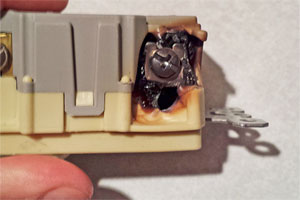 a blackened and burned-out GFCI breaker held between a finger and thumb