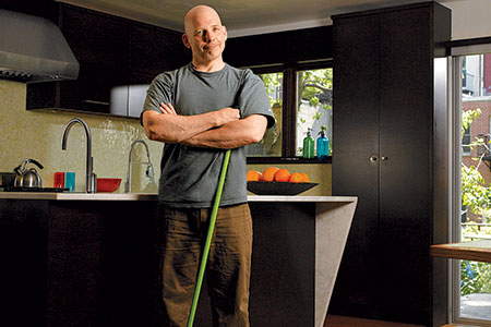 Scott Omelianuk in his kitchen with a broom