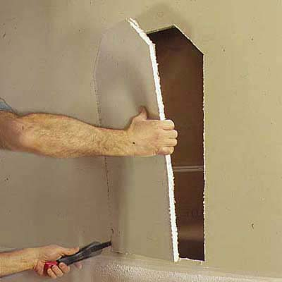 cutting into drywall between beams to make space for niche