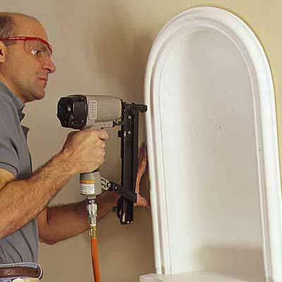using a pneumatic nailer to nail the niche into place with minimal dings