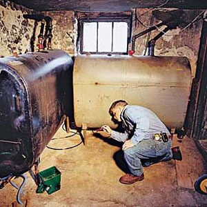 Tom Silva checks an oil tank during fall house inspection of East Boston project house