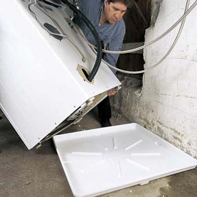 Technician installing a Drain Pan under a washer