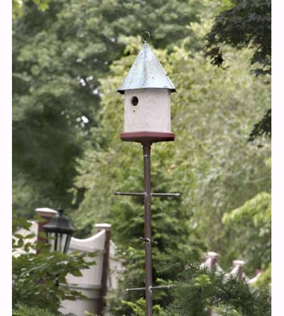 birdhouse with oxidized copper roof on metal pole with perches