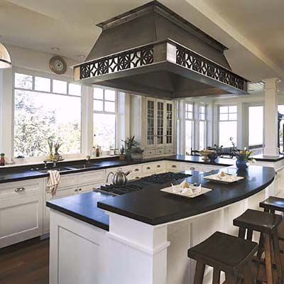 Island with cooktop and large decorative venthood
