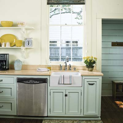 remodeled 1850s cottage kitchen with open shelves, off-white walls and pale green cabinets