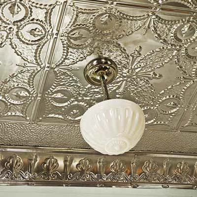 tin ceiling with a pendant light hanging from a medallion