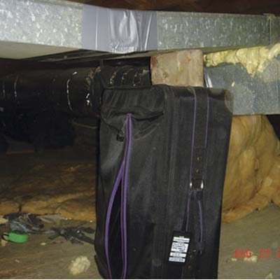 luggage and a brick supporting an HVAC duct in a crawlspace