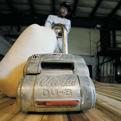 Jesse Hastings uses a large drum sander to smooth the Tiny Texas Chapel's tongue-and-groove floor