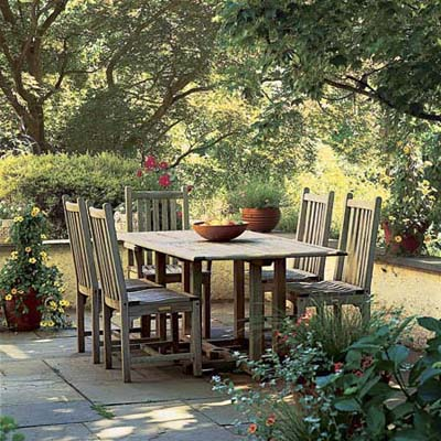 Stone patio with table, chairs and shrubs and vines around