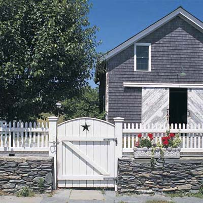 Gate and white picket fence in front of a gray house
