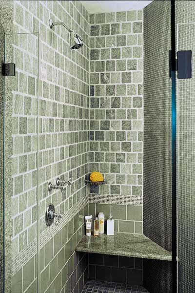 Shower has a curved wall and built-in seating and a glass door
