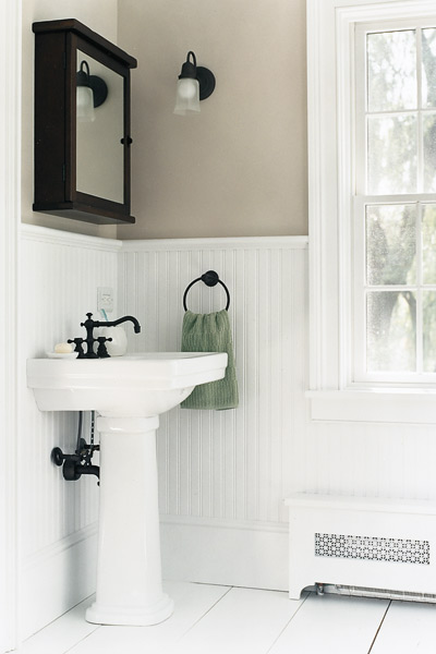 An old-fashioned pedestal sink from Toto, a Pottery Barn medicine cabinet, and a sconce from Restoration Hardware