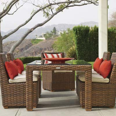 faux wicker patio furniture with red and whit cushions and pillows