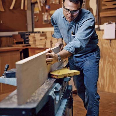 David Moser passes cherry boards through planer to straighten and square edges