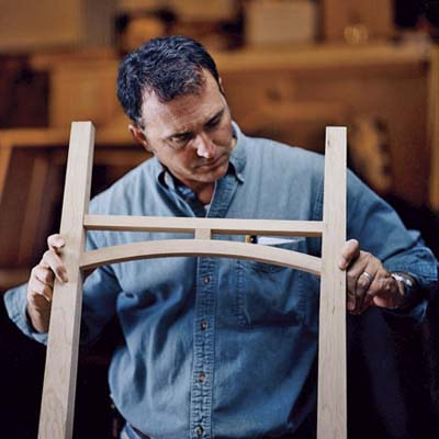 David Moser inspects the assembled curved stretcher for the heirloom dresser
