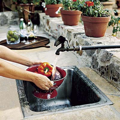 Stainless steel sink and copper faucet in outdoor kitchen