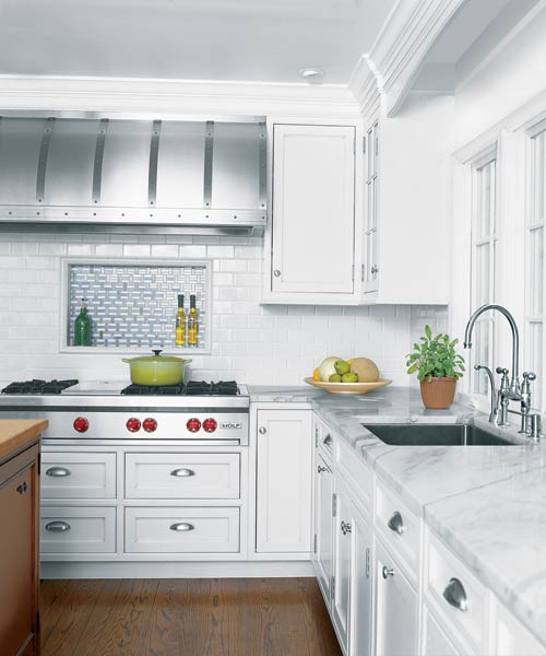 kitchen after remodel with white cabinetry, pale-marble countertops, studded steel range hood