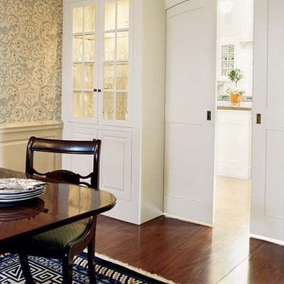 built-in cabinet and arched pocket doors in dining room of rehabbed 1834 farmhouse