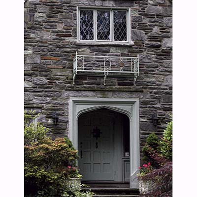 a Tudor arch frames a recessed panel front door