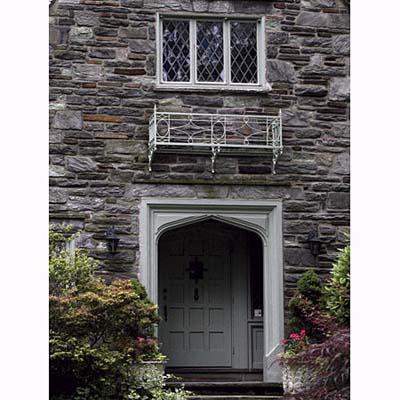 a Tudor arch frames a recessed panel front door