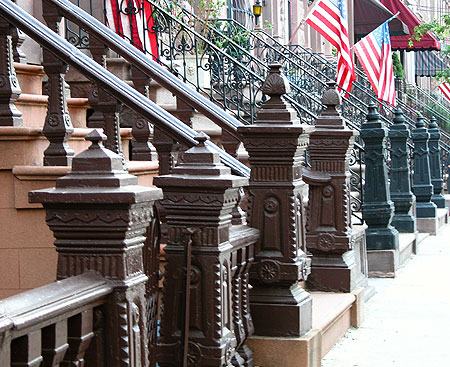 Cast-iron newel posts punctuate a lane of rowhouses.
