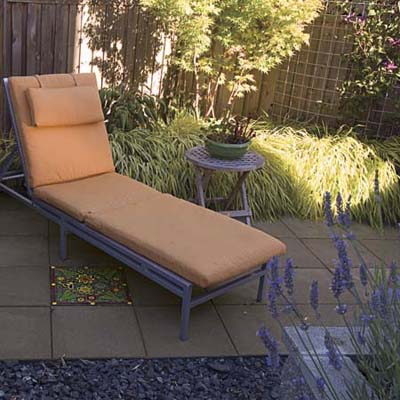 chaise lounge on a small patio with accent pavers