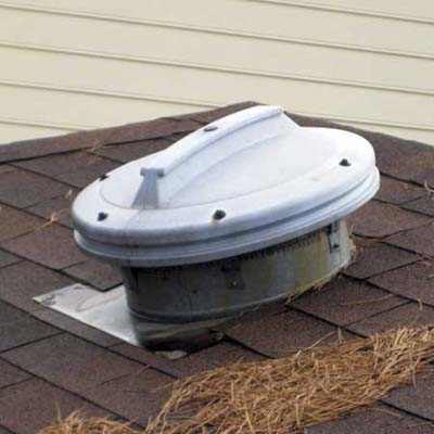 garbage can lid used as an external cover for an attic fan hood