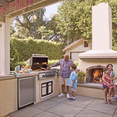 outdoor kitchen with man, woman and 3 kids