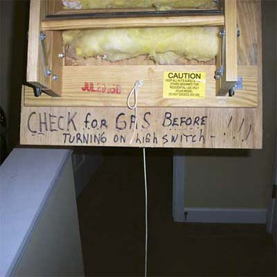 handwritten sign in a unlit attic asking people to not turn on the light for fear of a gas explosion