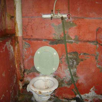 a toilet in a basement sitting underneath a hose spigot
