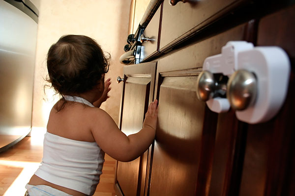 young child reaching up and over for a burner knob on top of a kitchen range