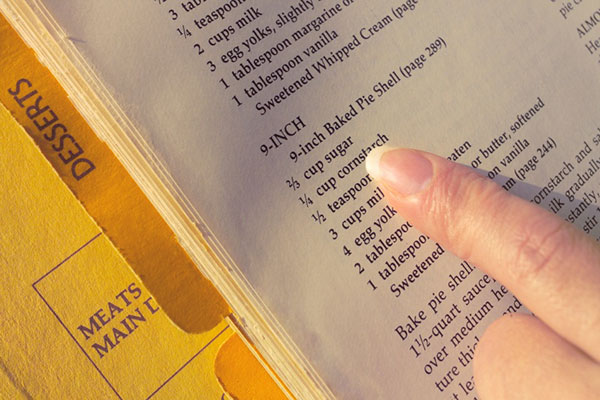 finger pointing to a recipe in an organized recipe binder