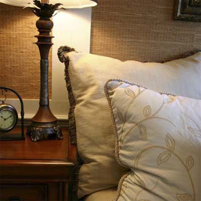close-up image of pillows nightstand clock and lamp in a guest bedroom