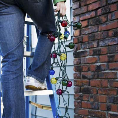person standing on a ladder to hang christmas lights