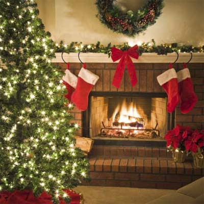 decorated living room with blazing fire, lit tree and hanging stockings