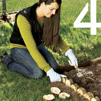 woman using discs cut from a christmas tree trunk to edge a flowerbed