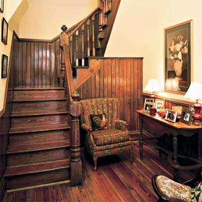 stairway surrounded by dark wood wainscoting