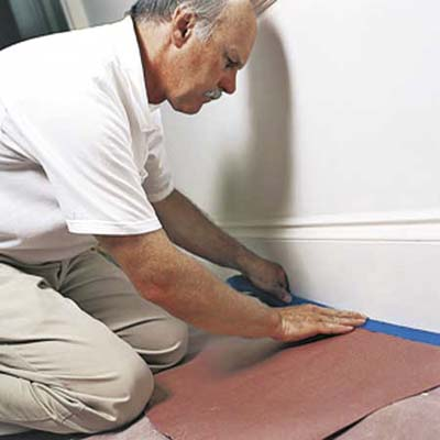 man taping down an area to paint