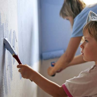 child painting a wall blue with adult supervision