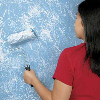woman using a faux finishing roller to apply blue paint to a wall